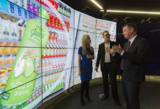 Victorian Government Minister for Industry and Employment, The Hon. Wade Noonan MP (far right), with Elesha Kelly and Daryl Thomson from the Food Innovation Centre at Monash. This was taken in Monash University's world-leading immersive visualisation space, Cave 2. The facility will enable companies to visualise their products on the market shelves in both Asia and Australia. Image Credit: Greg Ford.